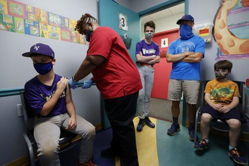 Family members watch as a 12-year-old is inoculated with Pfizer's vaccine against COVID-19 at Dekalb Pediatric Center in Decatur, Ga., on May 11, 2021. (Chris Aluka Berry/Reuters)